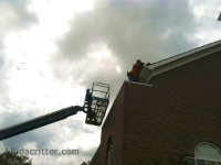 Man on a roof and cherry picker at a bat removal job at a church in Bowdon, Georgia