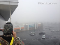 Man working up high sealing bats out of a commercial building on a foggy day