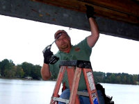 Technician performing bat removal at a boat house on Lake Sinclair