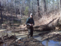 Man standing in a stream doing beaver control in Carrolton GA