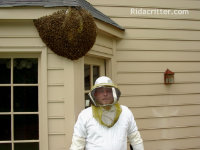 Man in bee suit standing in front of a home with a bee hive in Fairfield, Alabama
