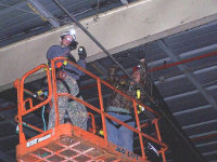 Two men doing bird control work in a warehouse in Bessemer, Alabama