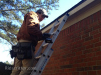 A man on a ladder performing a flying squirrel removal job in Roswell, GA