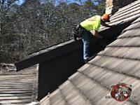 Man on a roof sealing flying squirrels out of the attic of a house in Birmingham Alabama