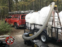 Huge filter bag on a flatbed truck being pumped full of contaminated insulation through a hose so it can be properly disposed of