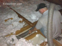 Man with machine installing blown-in insulation in an attic of a house in Pell City