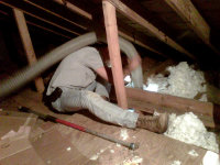 Man in an attic in Rockdale, Georgia replacing insulation contaminated by animals