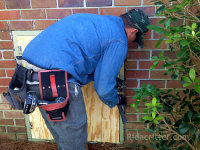 A man installing a new crawl space door at an Anniston, Alabama raccoon damage repair job