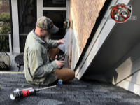 Bearded man sitting on the roof using tin snips to cut hardware cloth to seal squirrels out of the attic of a house in Acworth Georgia.