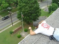 Bat control technician lying on a high roof, facing down, performing bat control and  bat proofing in Marietta, Georgia.